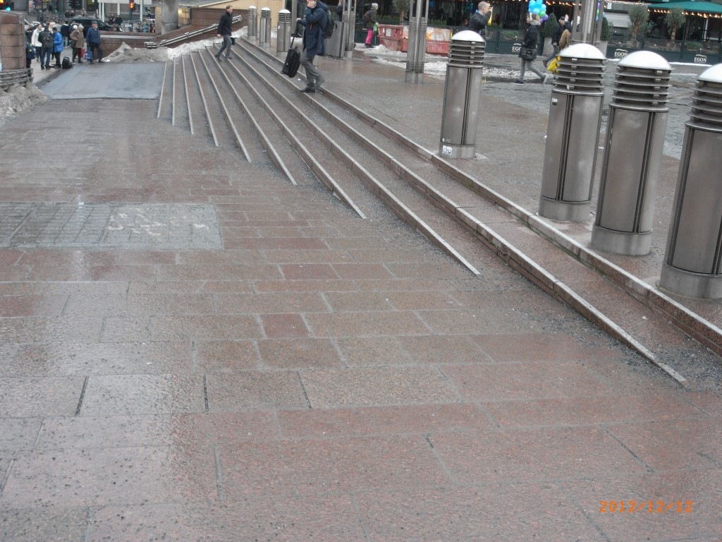 Image shows the approach to an Oslo train station. In the background are shallow stairs, marked with reflective borders and textured grip. In the foreground is a shallow ramp to the same level