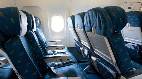 Image shows a row of a typical economy class airplane seats. Leg room is cramped, arm rests divide the seats. No humans are present.